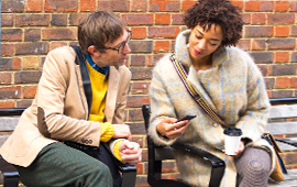 Two individuals discussing digital marketing on a mobile device